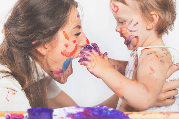 Feliz mamá y bebé jugar con rostro pintado por pintura - foto de stock