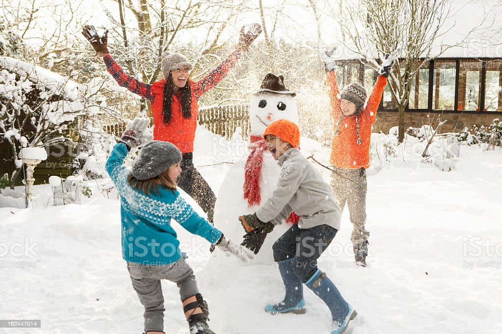 Happy mom and children building snowman in yard stock photo