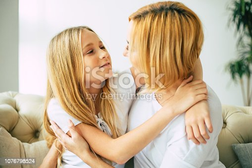 641288086istockphoto Happy mom and daughter at home 1076798524