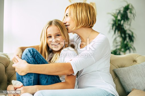 641288086istockphoto Happy mom and daughter at home 1076798568