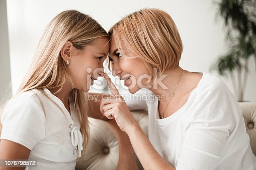 641288086istockphoto Happy mom and daughter at home 1076798572