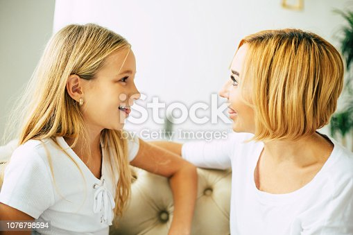641288086istockphoto Happy mom and daughter at home 1076798594