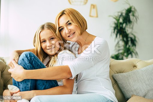 641288086istockphoto Happy mom and daughter at home 1076798596