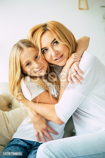 641288086istockphoto Happy mom and daughter at home 1076798600