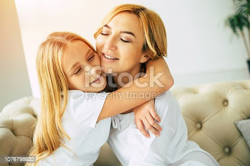 641288086istockphoto Happy mom and daughter at home 1076798632