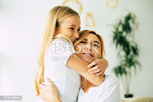 641288086istockphoto Happy mom and daughter at home 1076798642