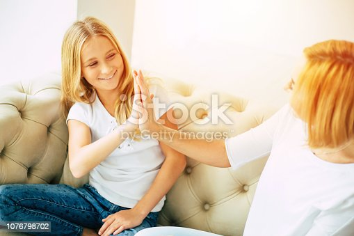 641288086istockphoto Happy mom and daughter at home 1076798702