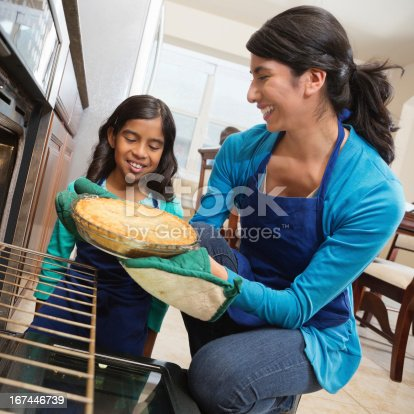 istock Happy mom and daughter baking apple pie together in kitchen 167446739