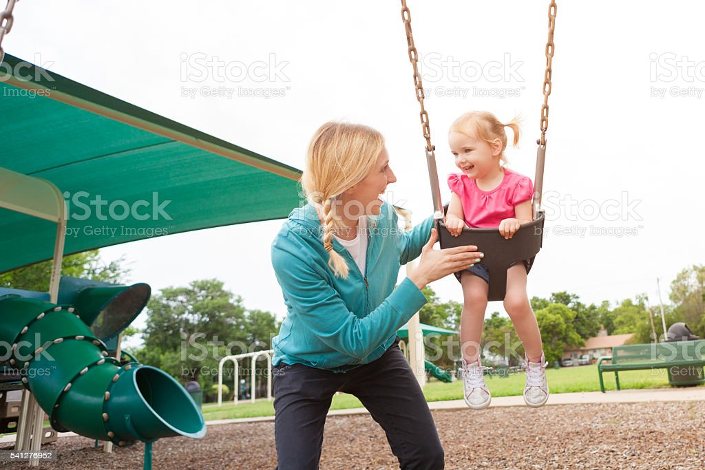 Happy mom and daughter play on the swing at playground stock photo
