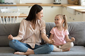 istock Happy mom and daughter practice yoga at home together 1204066341