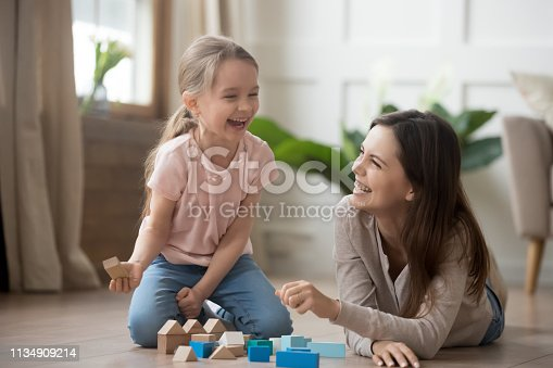 Happy family mom baby sitter and little kid daughter laughing playing with wooden blocks sit of warm floor, joyful mother having fun with child girl enjoy funny activity laughter at home together