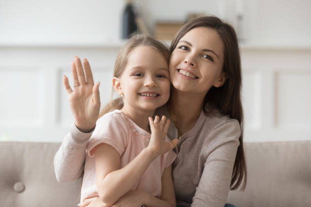 Happy mom and little daughter look at camera waving Portrait of smiling young mom hold hugging cute preschooler daughter look wave to camera, happy mother or nanny cuddle with little girl child shoot record video blog say hello to viewers young girls on webcam stock pictures, royalty-free photos & images