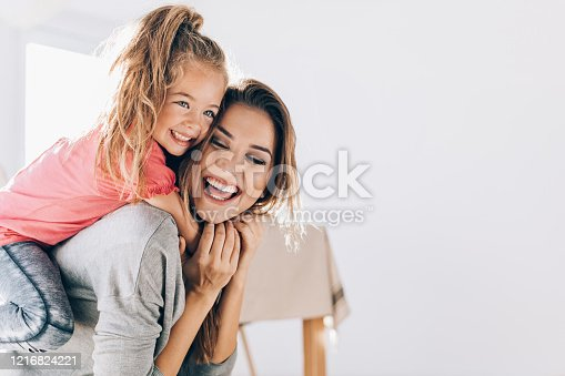 Happy mother and daughter playing and embracing at home
