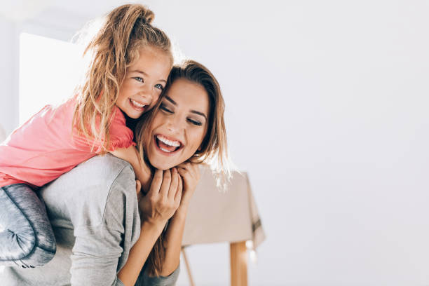 feliz mamá llevando a su pequeña hija - hija fotografías e imágenes de stock