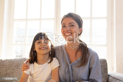 1070262182 istock photo Happy mom embracing little kid daughter looking at camera webcam 1130696770