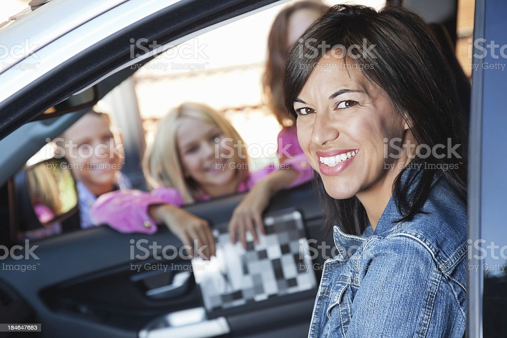 Happy mom picking up her children from school stock photo