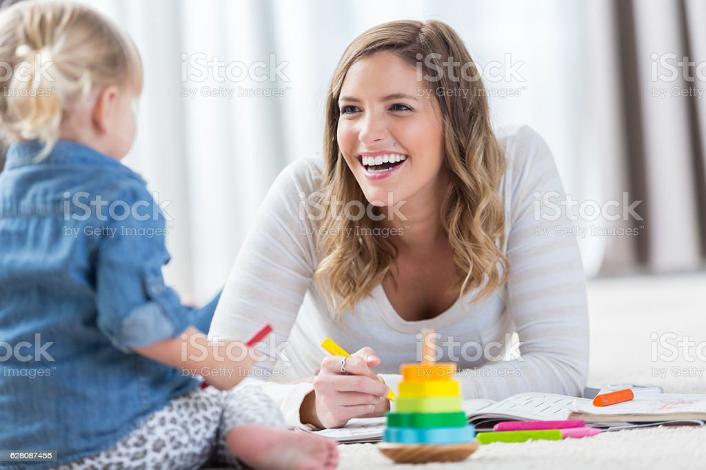 Happy mom plays with toddler daughter at home stock photo