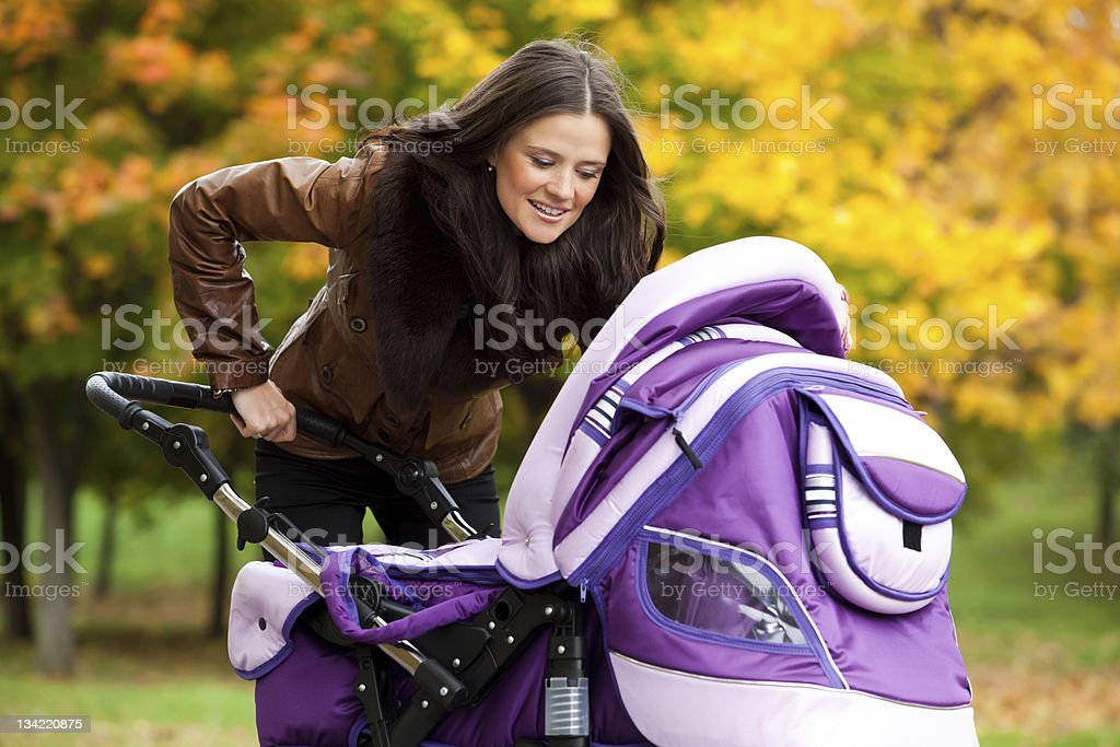 happy mom with stroller walks in park stock photo