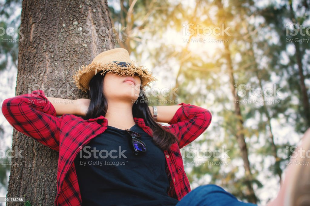 Happy moment hipster woman relaxing and sitting under the big tree on park ,enjoying time on holiday concept ,color of vintage tone and soft focus royalty-free stock photo