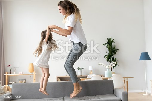 Happy mommy and kid daughter holding hands jumping on sofa together, baby sitter or mother playing having fun with cute kid girl at home, young mum and child enjoy spending time laughing together