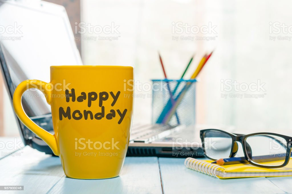 Happy Monday motivational text on yellow morning coffee cup near computer at office workplace. Business background stock photo