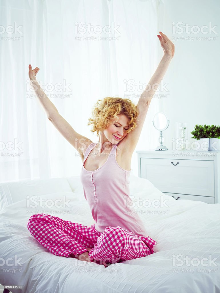 Happy morning Happy young adult woman sitting cross-legged on a bed in the morning and stretching her arms. 20-24 Years Stock Photo