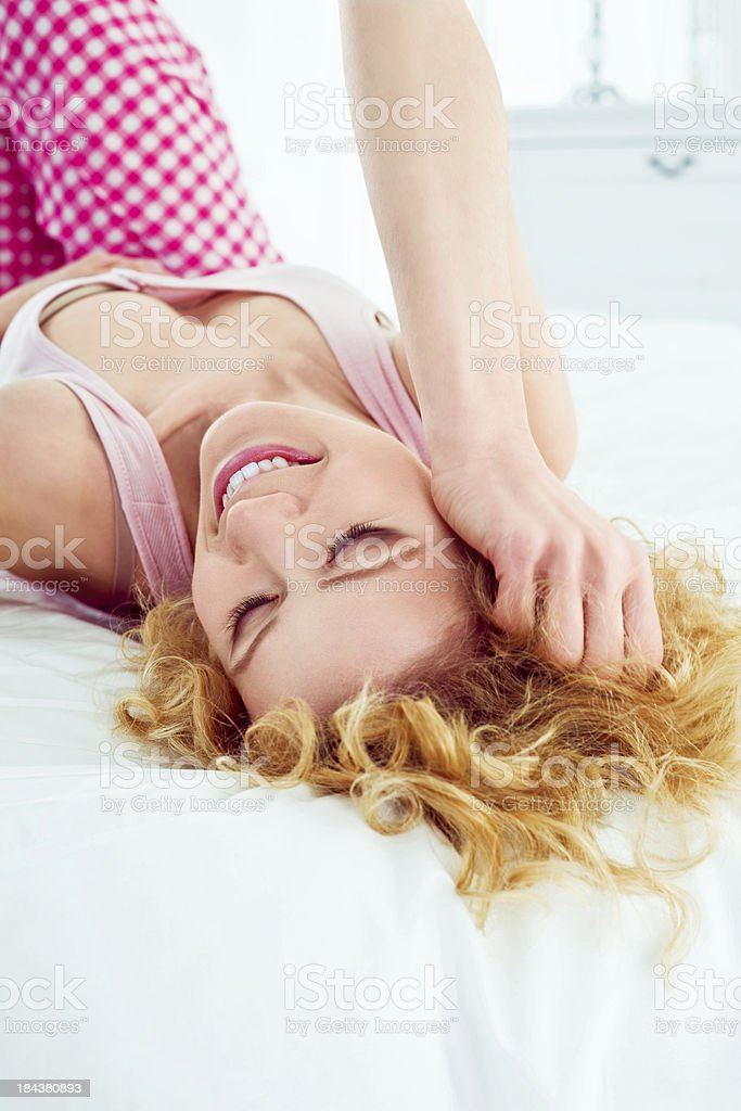 Happy morning Happy young adult woman lying down in a bed in the morning and laughing. 20-24 Years Stock Photo