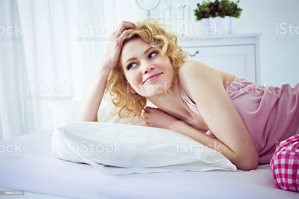 "Happy morning ""Happy young adult woman lying down in a bed in the morning, looking away and laughing."" 20-24 Years Stock Photo"