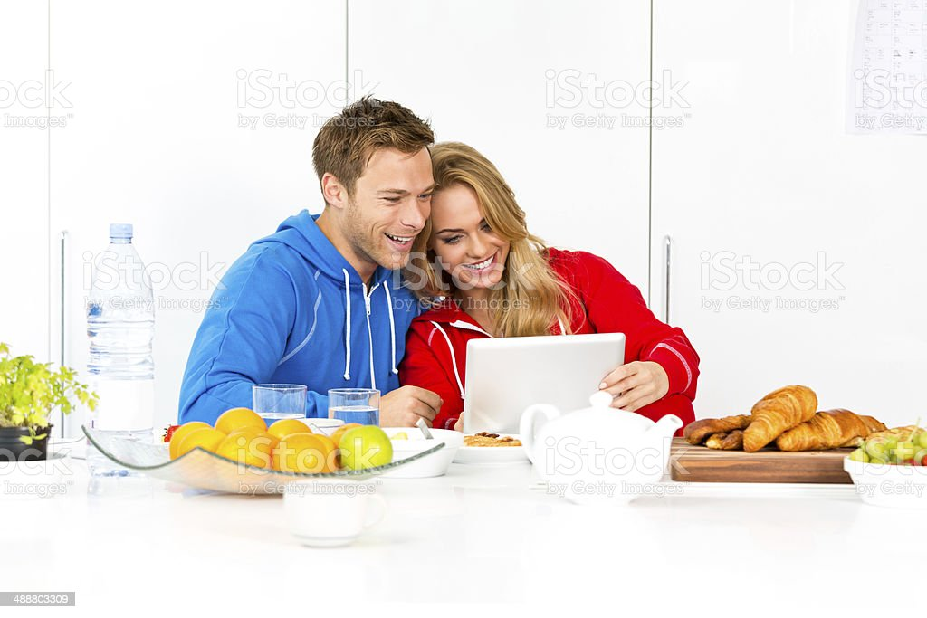 Happy morning Happy young couple sitting in the modern kitchen in the morning, using a digital tablet during breakfast.  20-24 Years Stock Photo
