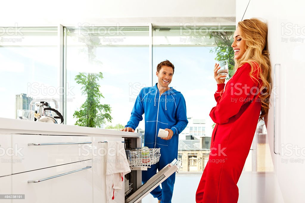Happy morning Happy young couple standing in the modern kitchen in the morning. Young man putting dishes into dishwasher. 20-24 Years Stock Photo