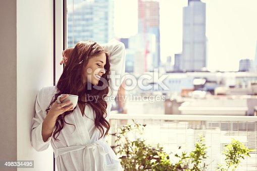 Beautiful young woman wearing white bathrobe relaxing with cup of coffee in her apartment in the morning.