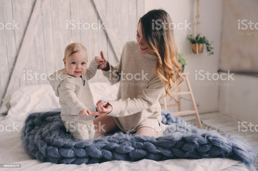 Happy Mother And 8 Month Old Baby Playing Relaxing At Home In Bedroom The