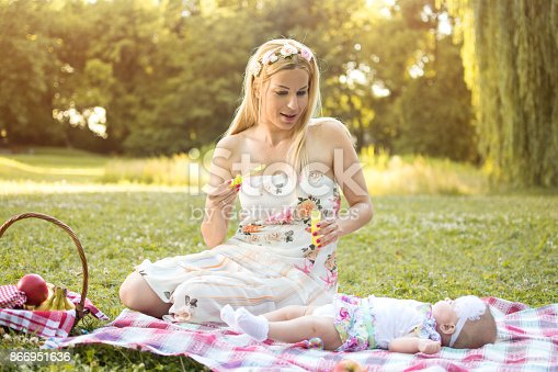 507271044istockphoto Happy mother and baby enjoying free time together in park. 866951636