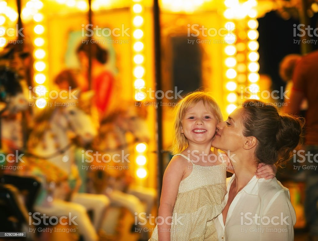 Happy mother and baby girl in front of carousel stock photo