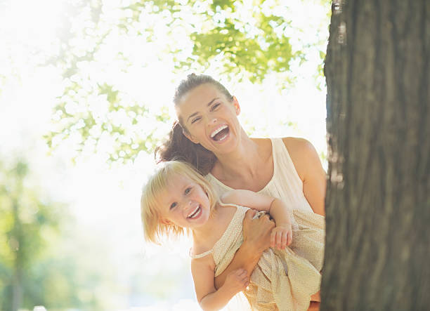happy mother and baby looking out from tree - mom spying stock photos and pictures