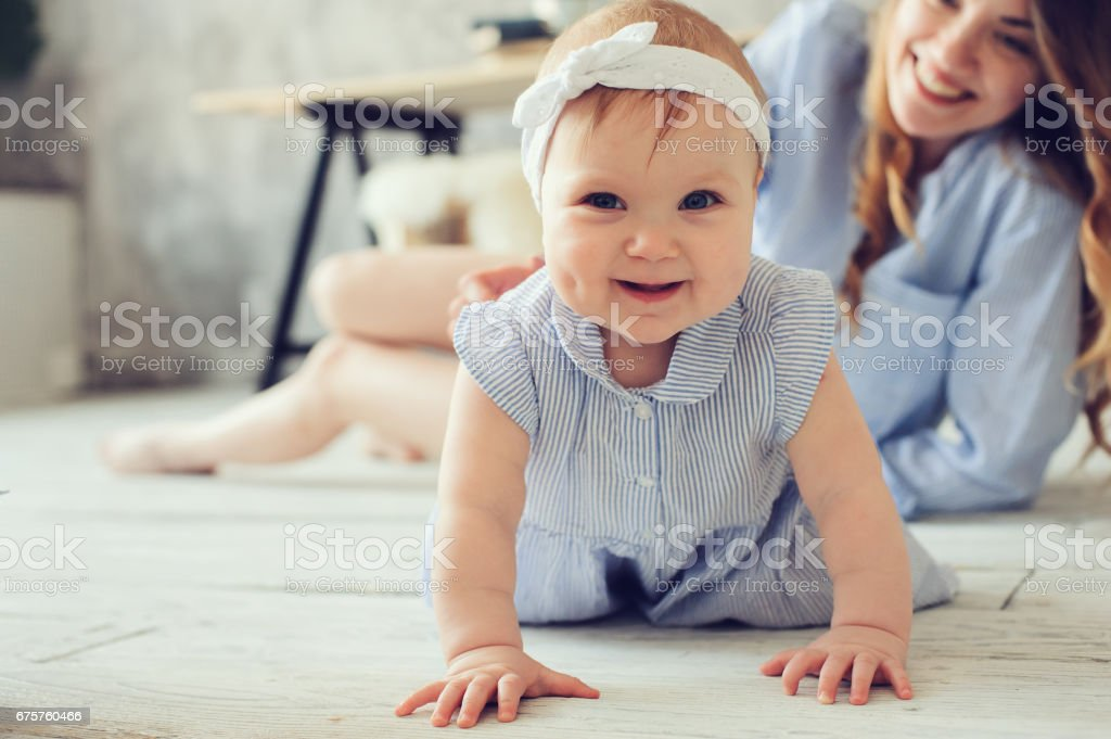 happy mother and baby playing at home in bedroom. Cozy family lifestyle in modern scandinavian interior. stock photo