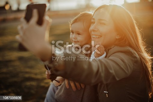 istock Happy mother and baby taking self-portrait on smartphone in sunn 1087035926