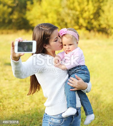 istock Happy mother and baby taking self-portrait on smartphone in sunn 499730018