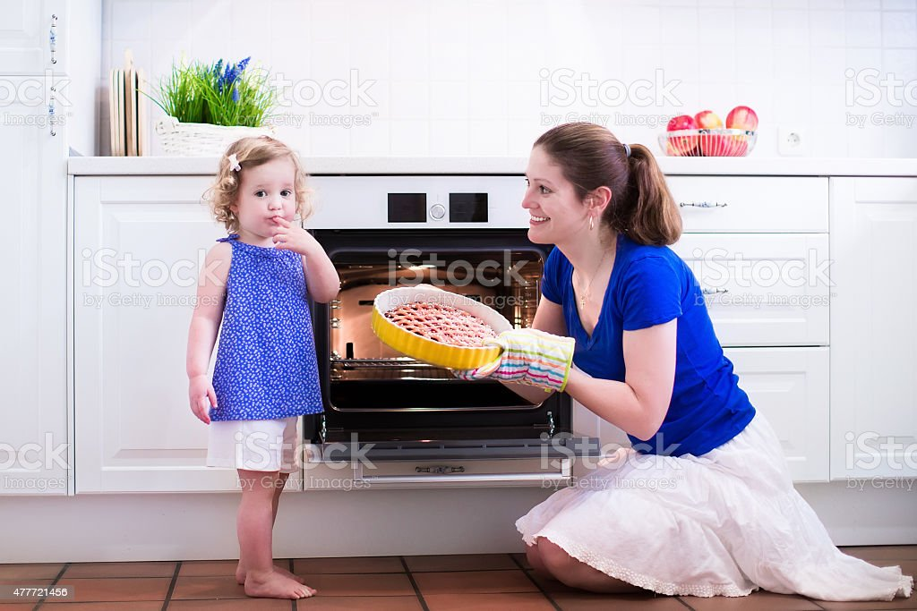 Happy mother and child baking a cake. stock photo