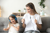 Happy young mother and funny child daughter having fun laughing dancing sitting on couch listening to music in earphones together, smiling mom and kid wearing headphones enjoy favorite songs at home