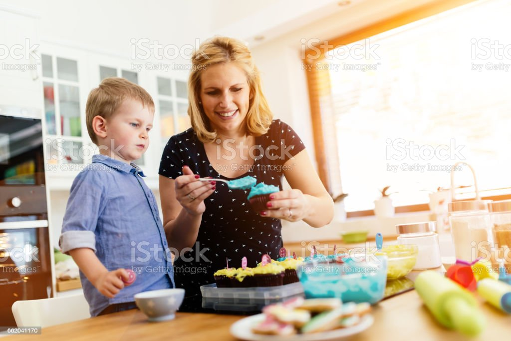 Happy mother and child in kitchen preparing cookies royalty-free stock photo