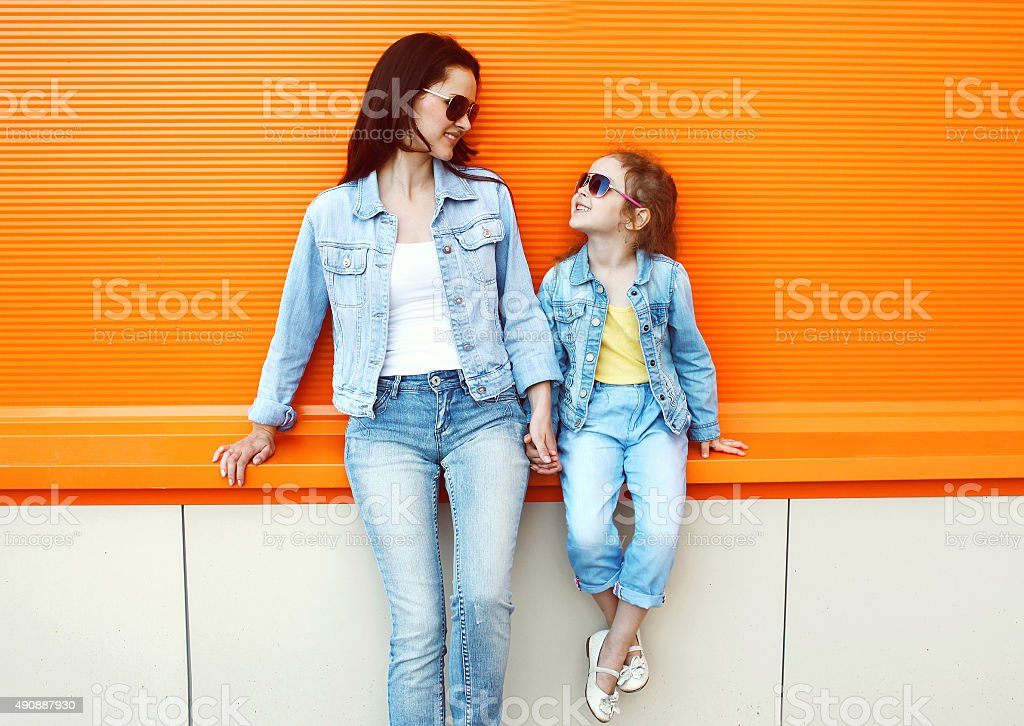 Happy mother and child wearing a jeans clothes in city stock photo