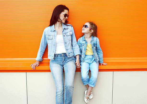 glückliche mutter und kind mit einer jeans kleidung in der stadt - mode herbst 2015 stock-fotos und bilder