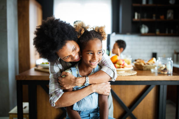 Happy mother and children in the kitchen. Healthy food, family, cooking concept stock photo