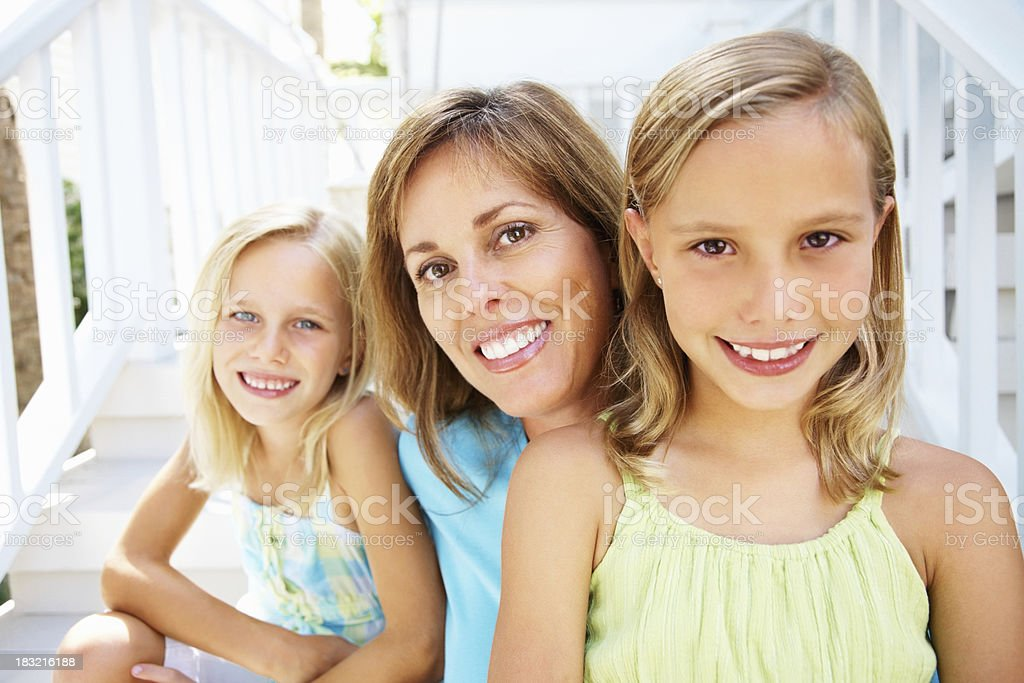 Happy mother and children sitting in front of their house royalty-free stock photo