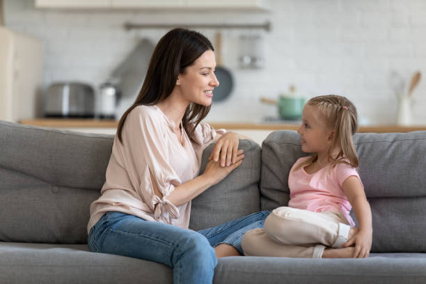 Happy mother and cute child enjoy talking relaxing on sofa stock photo