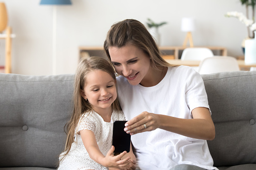 Happy mother and cute daughter laughing taking selfie on smartphone