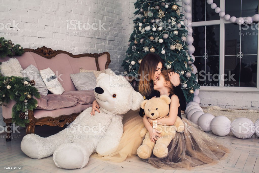 1ed59a3daa Happy mother and daughter are holding teddy bears on Christmas Eve.  royalty-free stock