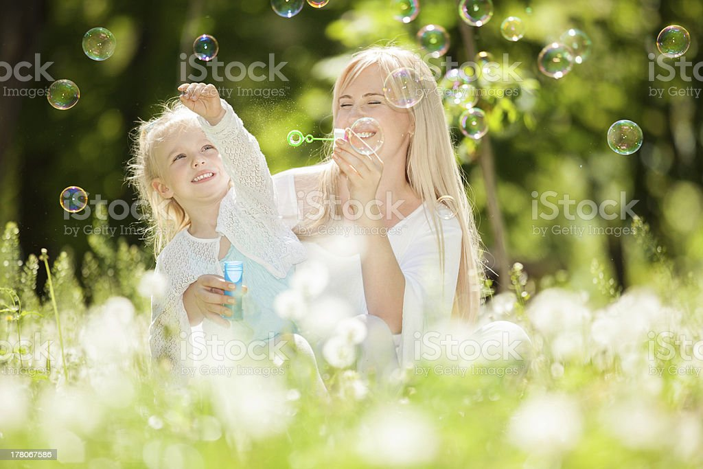 Happy mother and daughter blowing bubbles in the park royalty-free stock photo