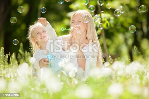 istock Happy mother and daughter blowing bubbles in the park 178067586